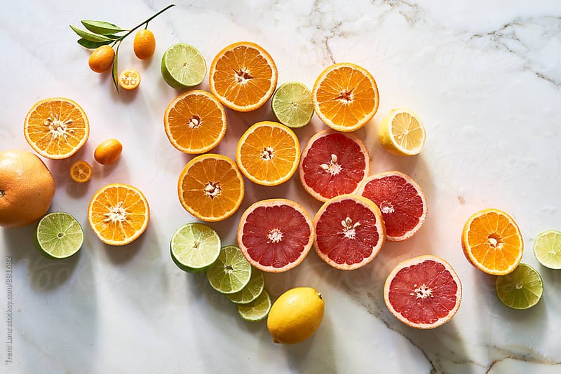 Cut citrus fruits for health and wellness on table by Trent Lanz for Stocksy United