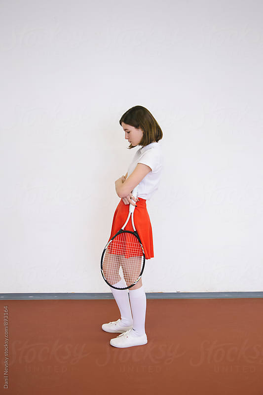 Woman with crossed hands holding tennis racket by Danil Nevsky for Stocksy United