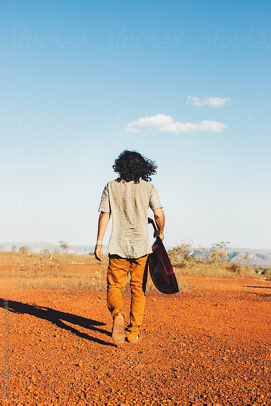 Long-Haired Man Holding Oud (Mandolin) and Walking Alone in Beautiful Countryside by Julien L. Balmer for Stocksy United