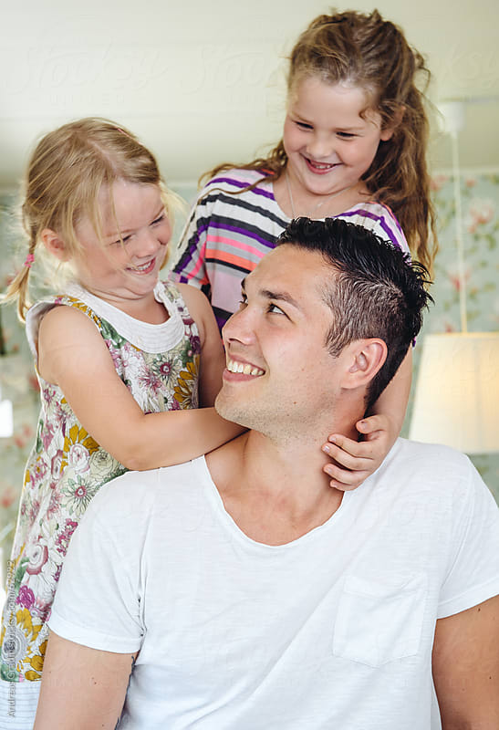 happy father with his daughters at home by Andreas Gradin for Stocksy United