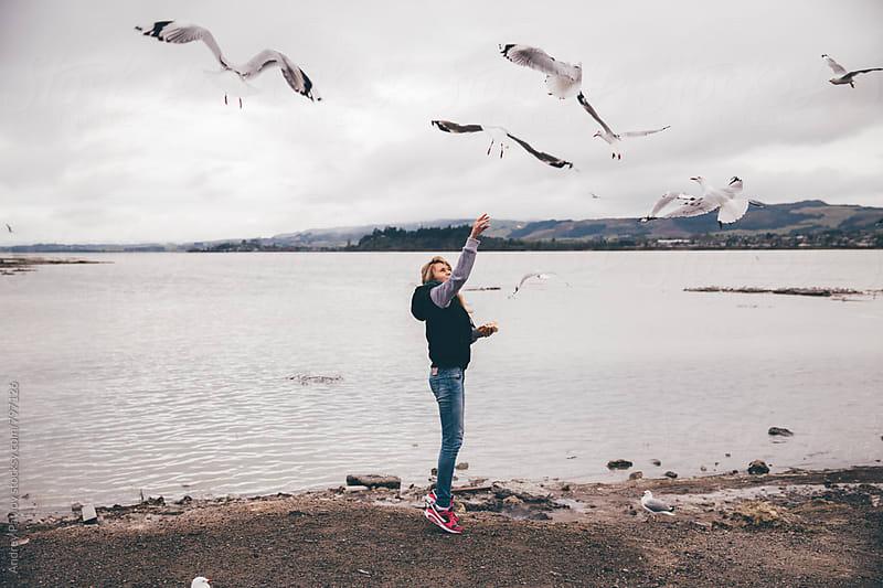 Woman feeding seagulls by Andrey Pavlov for Stocksy United