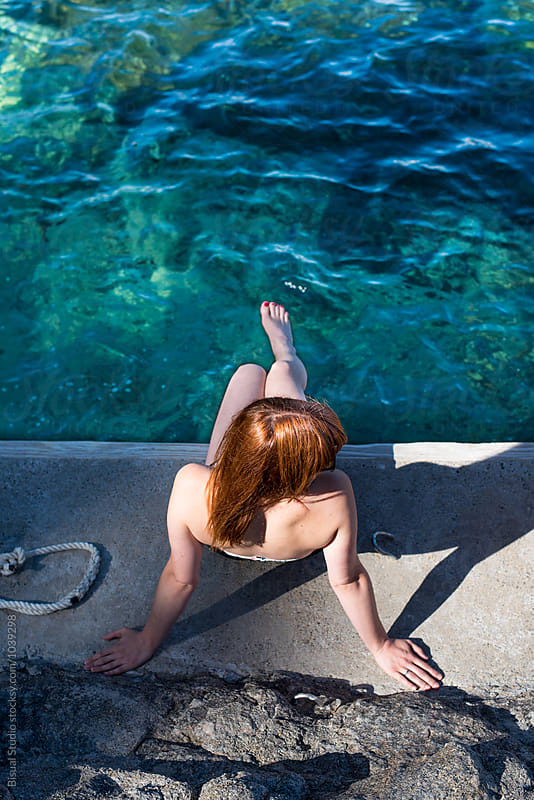 Red hair woman sitting on a pier in the mediterranean sea, Spain by Bisual Studio for Stocksy United