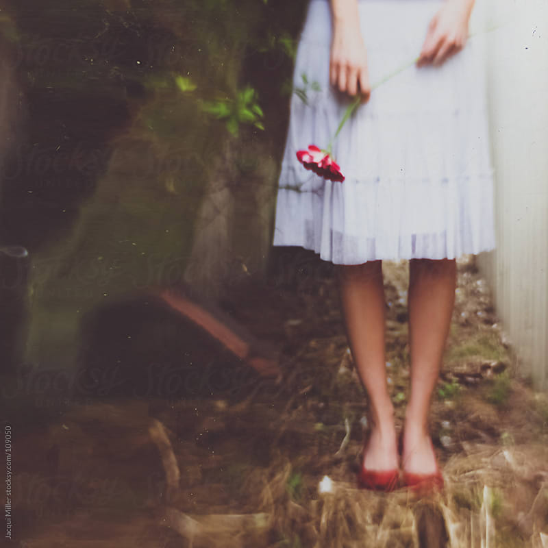 Whimsical shot of woman wearing red shoes and a white skirt, holding a red flower in her hands.  by Jacqui Miller for Stocksy United