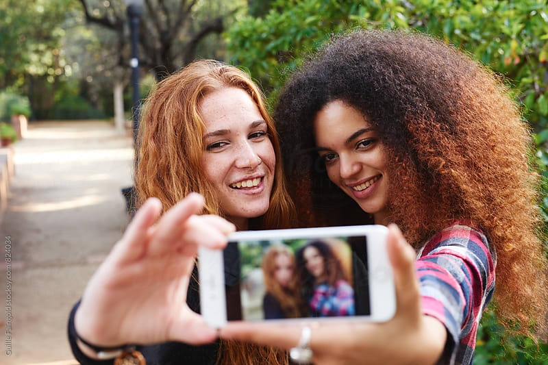 Two young girlfriends making selfie  by Guille Faingold for Stocksy United