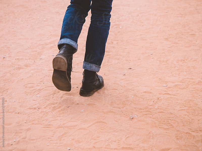 Hip anonymous male walking through desert dust in leather boots by Jeremy Pawlowski for Stocksy United