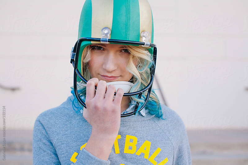 Pretty Girl Posing with Football and Helmet  by Gabrielle Lutze for Stocksy United
