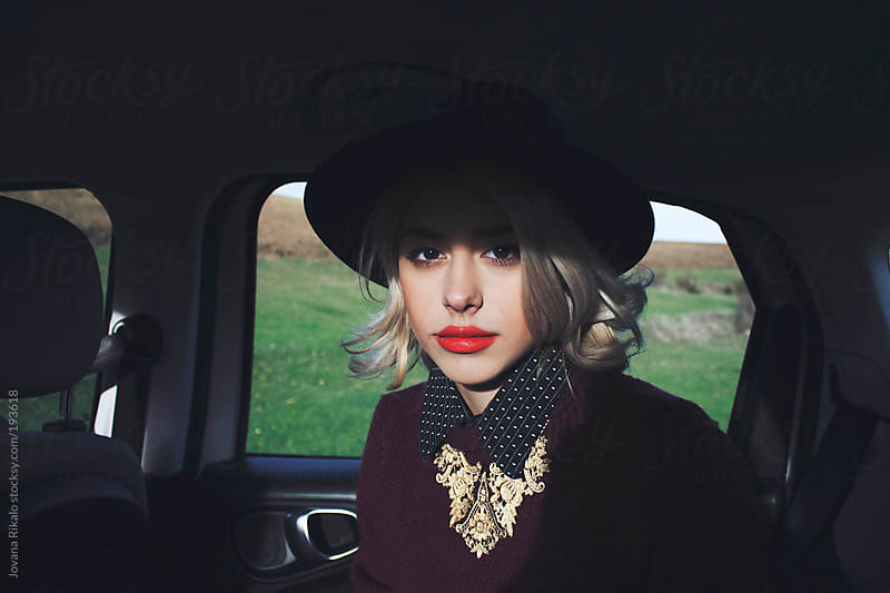 Young woman sitting in a car and looking at camera by Jovana Rikalo for Stocksy United
