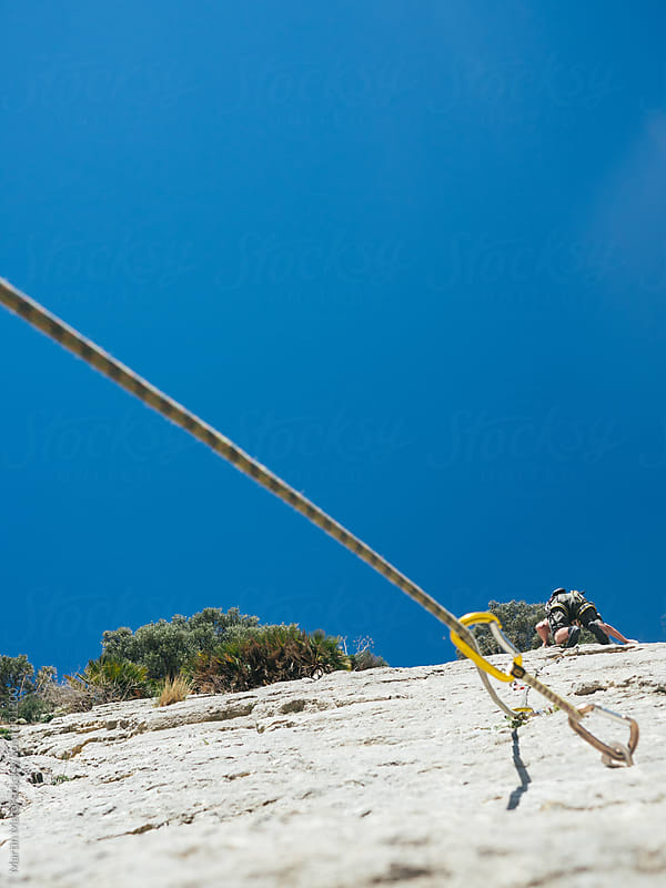 Rope leading to a climber on a rock by Martin Matej for Stocksy United