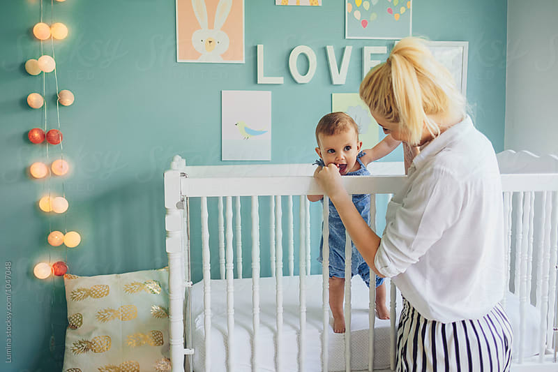 Woman Holding a Baby Girl in Her Crib by Lumina for Stocksy United