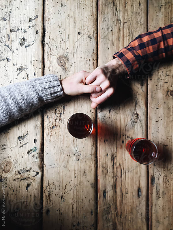 Man and woman holding hands with two beers on a wooden table by Suzi Marshall for Stocksy United