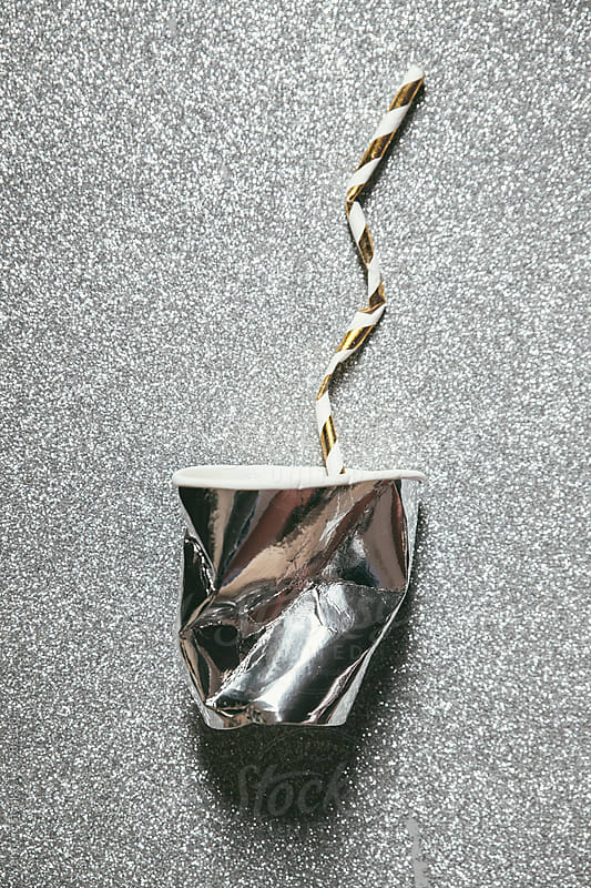 Destroyed silver paper glass and straw by Vera Lair for Stocksy United