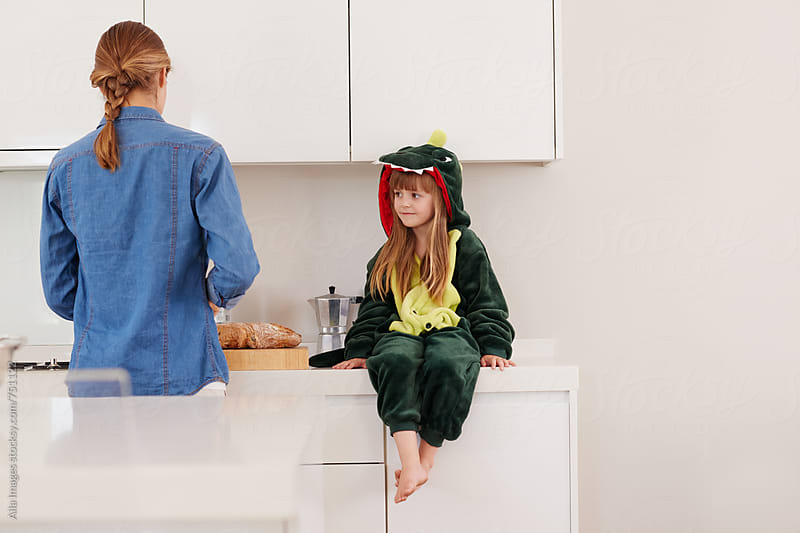 Cute daughter in dino suit in kitchen while mom is cooking by Aila Images for Stocksy United