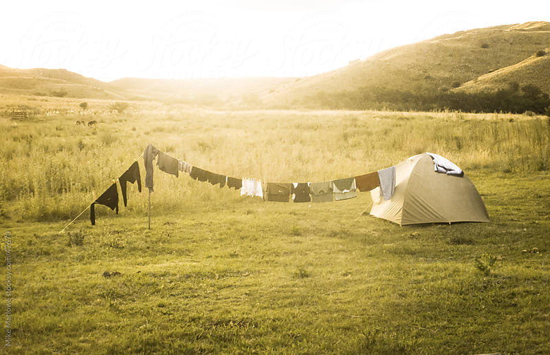 A backlit shot of a tent with washing hanging on a line by Mike Marlowe for Stocksy United