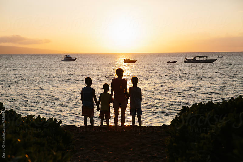 Family looking at sunset at the beach by Curtis Kim for Stocksy United