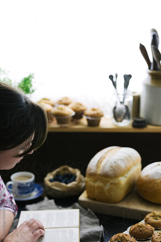 Woman reads old cookery book while bread and muffins cool by Kirsty Begg for Stocksy United
