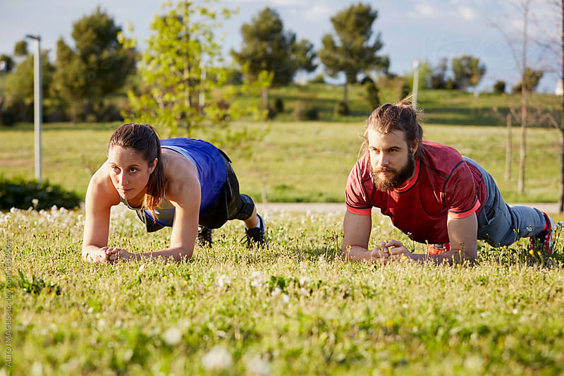 Determined Man And Woman In Plank Position In Park by ALTO IMAGES for Stocksy United
