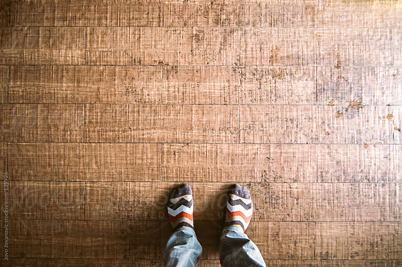 Looking down on feet standing on a wooden floor. by Jovo Jovanovic for Stocksy United