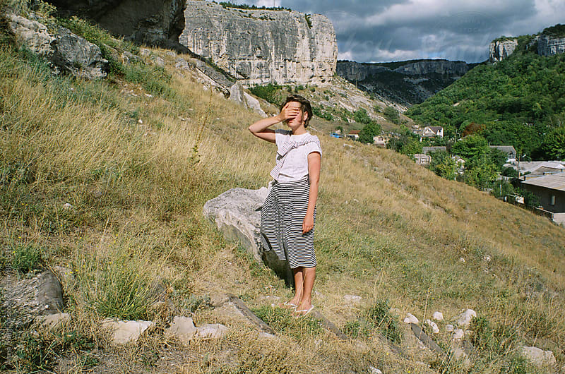 A film portrait of young woman closing her eyes in the mountain of Crimea by Anna Malgina for Stocksy United