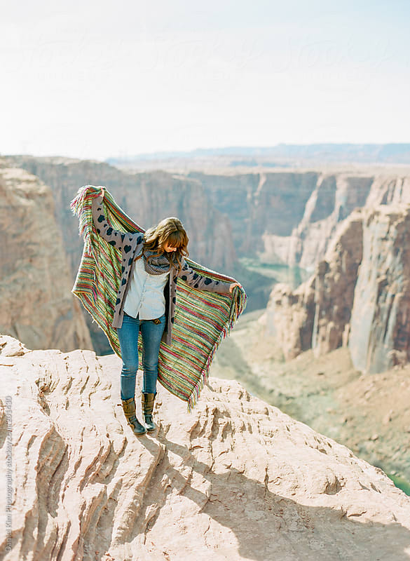 young woman holding up blanket overlooking canyon by Daniel Kim Photography for Stocksy United
