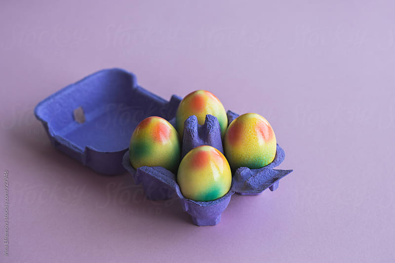 Colored eggs in a purple box on a purple background by Irina Efremova for Stocksy United