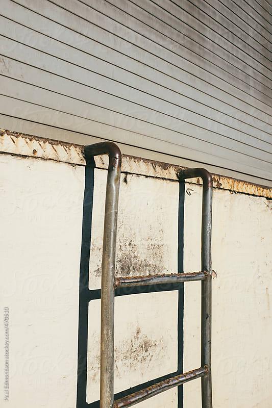 Ladder reaching towards warehouse doorway by Paul Edmondson for Stocksy United