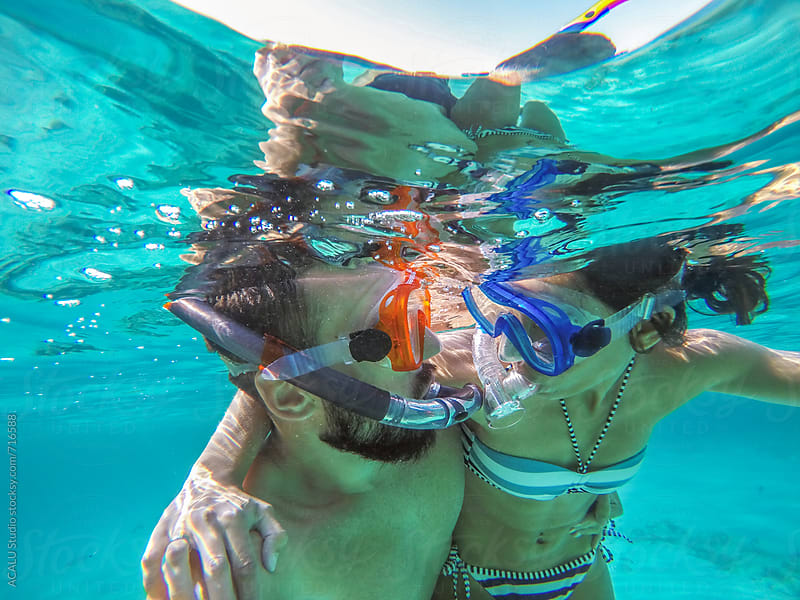 Young couple kissing with diving goggles by ACALU Studio for Stocksy United