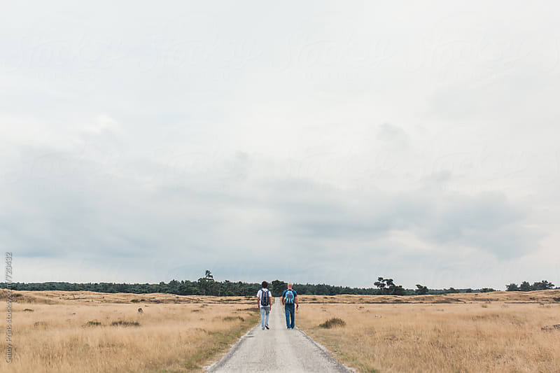 Two men hiking with backpacks on a long road in the fields by Cindy Prins for Stocksy United