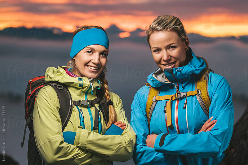 portrait of two beautiful blond sporty women in alpine scenery at sunset by Leander Nardin for Stocksy United