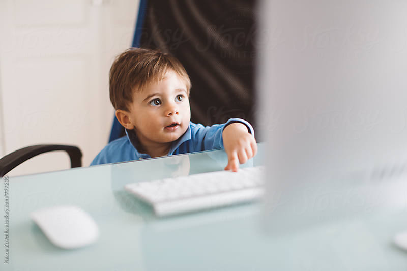 1 year old boy in front of a PC by Nasos Zovoilis for Stocksy United