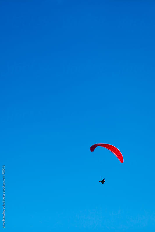 Image of the silhouette of a man paragliding against a bright blue sky by anya brewley schultheiss for Stocksy United
