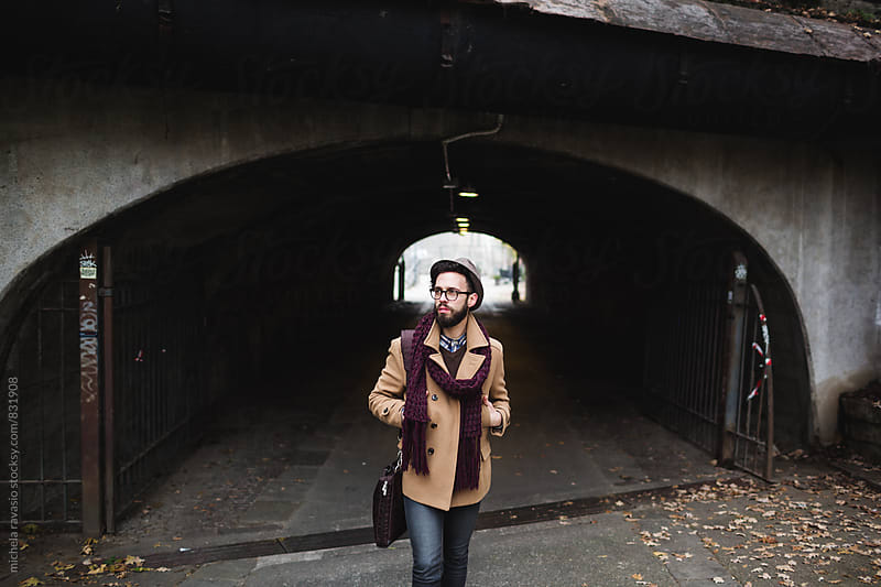 Young man walking around the city on a cold day by michela ravasio for Stocksy United