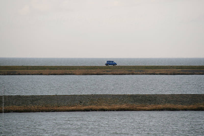 A blue car driving on a very small road surrounded by water in Flevoland, The Netherlands by Kaat Zoetekouw for Stocksy United