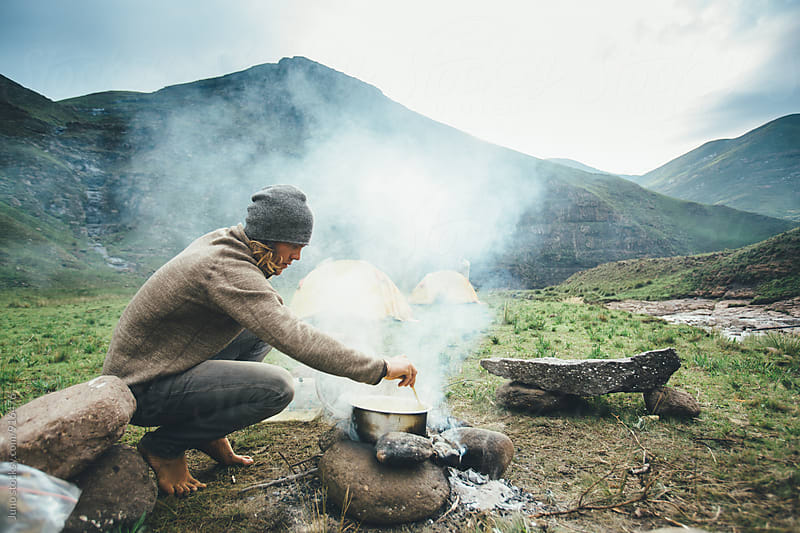 Man cooking on a camp fire at dawn by Micky Wiswedel for Stocksy United