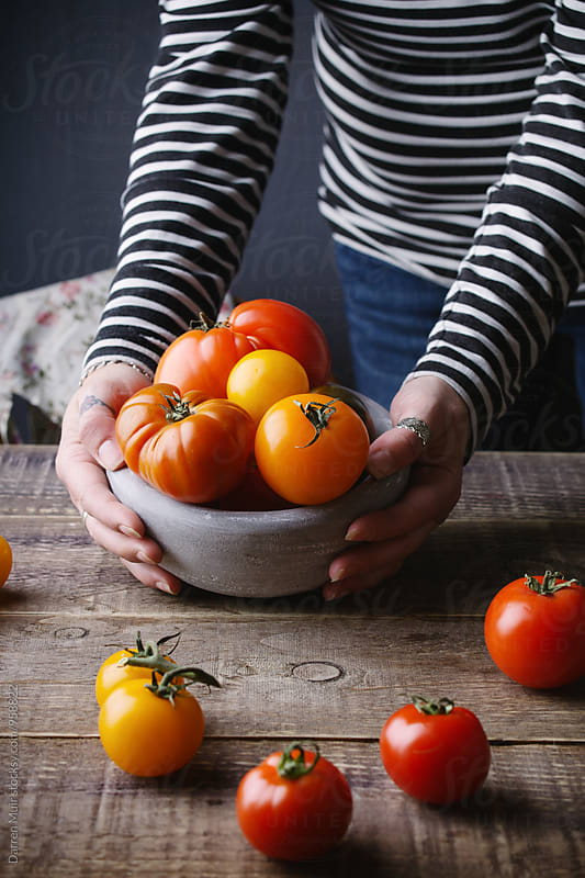 Woman placing a bowl of Heirloom or Heritage tomatoes onto a wooden table. by Darren Muir for Stocksy United