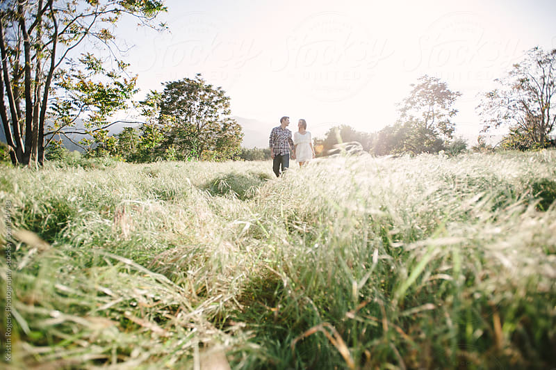 Married couple walking through field by Kristin Rogers Photography for Stocksy United