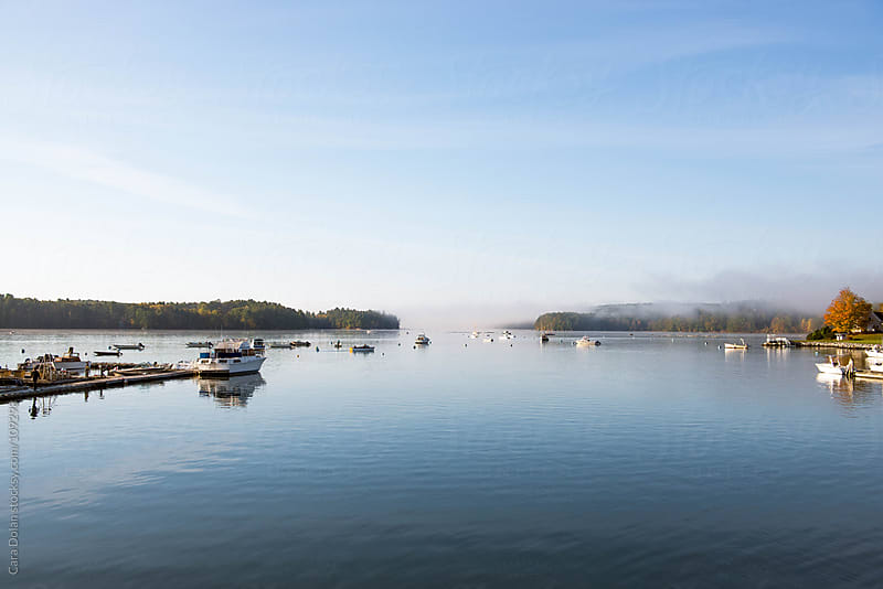 Morning fog lifts from the harbor of a small coastal town in autumn by Cara Dolan for Stocksy United