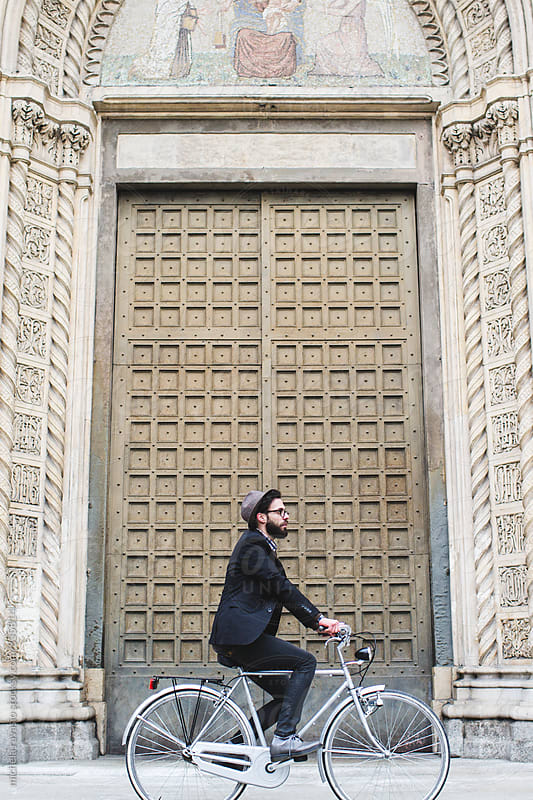Young man with hat on bicycle in front of an ancient door by michela ravasio for Stocksy United