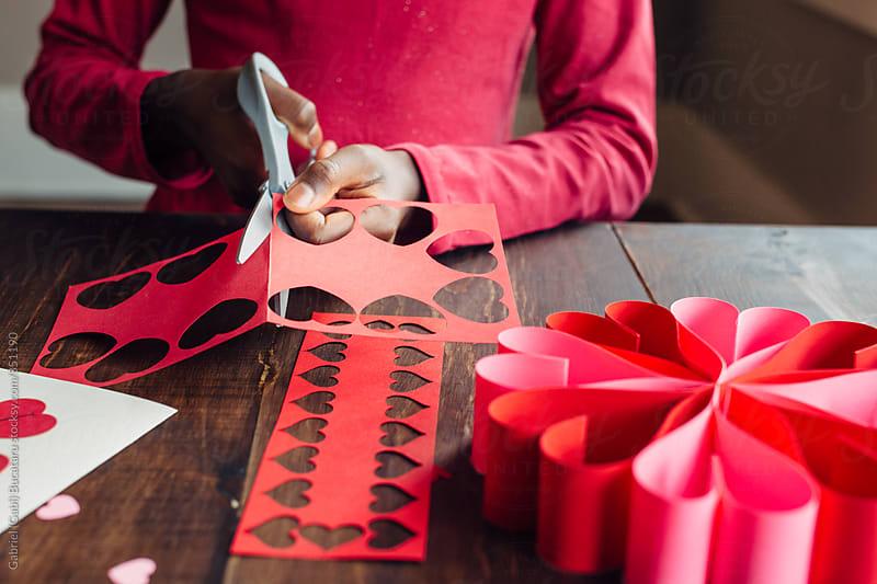 Black girl cutting red paper for Valentines by Gabriel (Gabi) Bucataru for Stocksy United