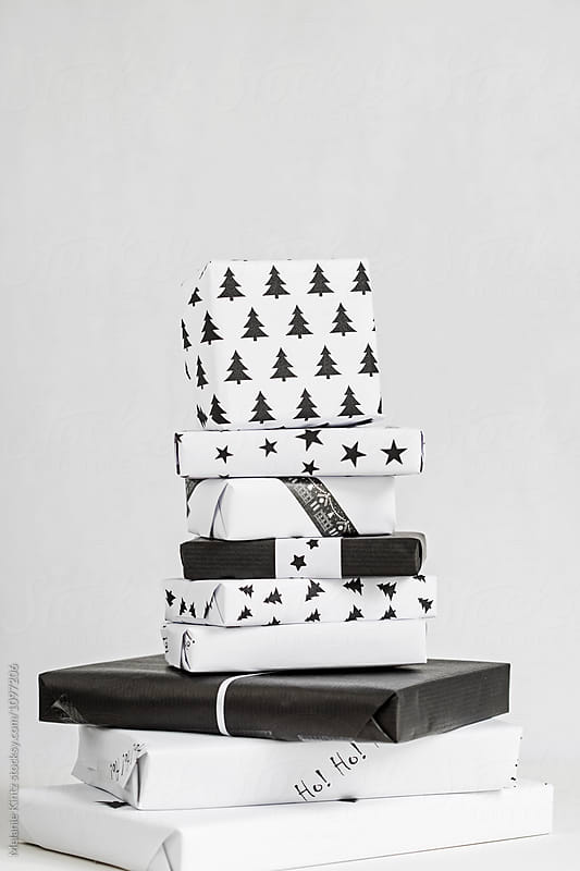 Stack of christmas presents wrapped in black and white by Melanie Kintz for Stocksy United