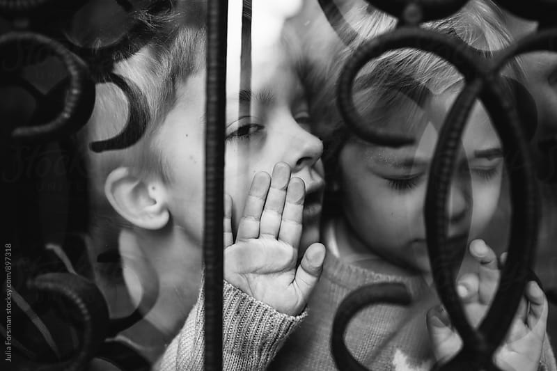 Brother annoying his sister behind a window. by Julia Forsman for Stocksy United