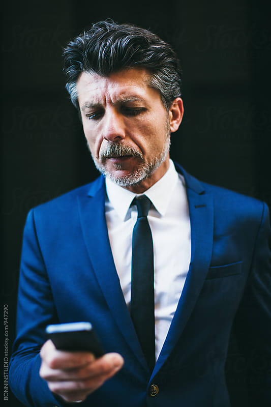 Portrait of a mature businessman using his smartphone on black background. by BONNINSTUDIO for Stocksy United