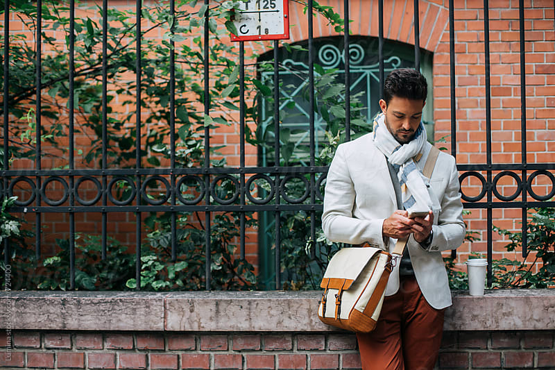 Stylish Man Texting on His Mobile Phone Outdoors by Lumina for Stocksy United
