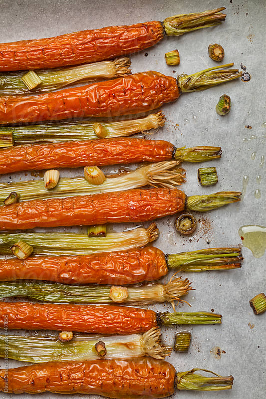 Roasted carrots and scallions on parchment by David Smart for Stocksy United