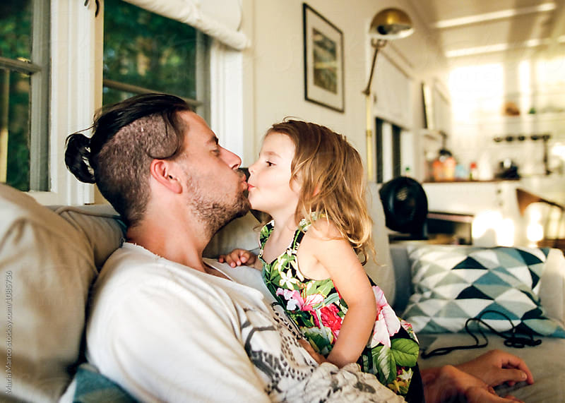 child giving her dad a kiss by Maria Manco for Stocksy United