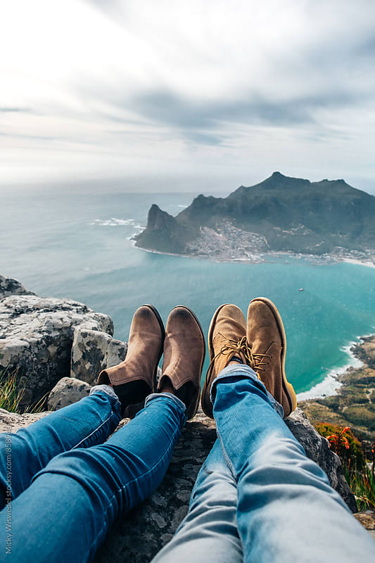 leather shoes and jeans of a relaxed hiking couple sitting at a mountain top by Micky Wiswedel for Stocksy United