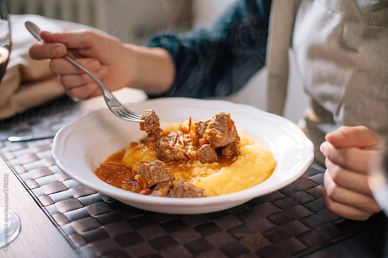 Eating beef stew with polenta by Davide Illini for Stocksy United