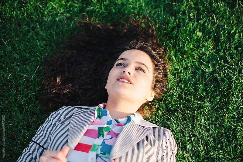 Woman lying on grass in a park by Marija Mandic for Stocksy United