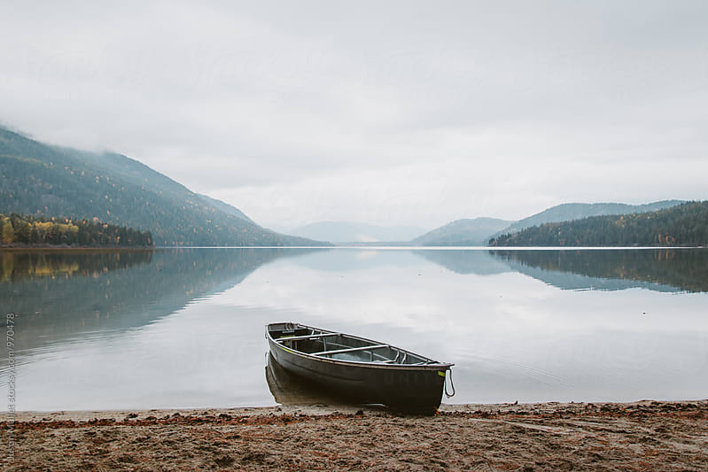 Canoe on the beach of a still mountain lake by Justin Mullet for Stocksy United