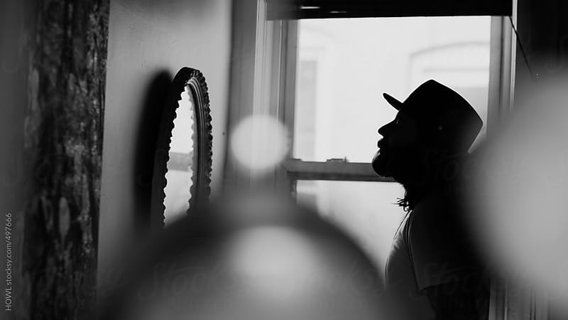 A bearded man in a hat stares intently into a mirror  by HOWL for Stocksy United
