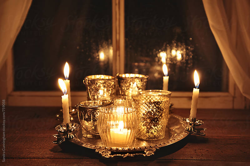 Burning candles on silver tray in window by Sandra Cunningham for Stocksy United